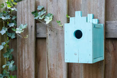 Blue birdhouse on a wooden fence Royalty Free Stock Image