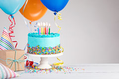 Blue Birthday Cake. Presents, hats and colorful balloons over light grey Royalty Free Stock Photo