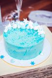 Blue birthday cake with a small meringues. And white snowflakes Royalty Free Stock Photos