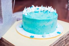 Blue birthday cake with a small meringues. And white snowflakes Stock Photos