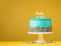 Blue Birthday Cake on Yellow. Blue buttercream birthday cake with colorful sprinkles over yellow background Royalty Free Stock Images