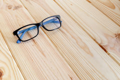 Blue and black glasses on wood table background.  stock images