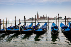Blue and black gondolas on canal Stock Photos