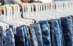 Blue and black jeans hanging with plastic hanker Royalty Free Stock Photos