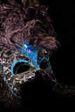 Blue Black Mask. A blue and black feathered mask covered with lace and sapphire blue gemstones on black background Stock Photos