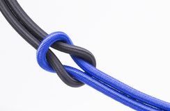 Blue and black string knotted on a white background. The image shows blue and black knotted, isolated on white stock photography