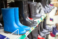Blue and black waterboots are on shop shelves Royalty Free Stock Photos