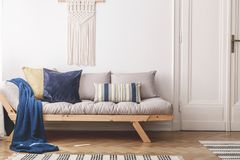 Blue blanket and cushions on beige wooden sofa in white loft interior with door. Real photo. Concept stock photo