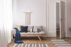 Blue blanket and pillows on wooden couch in white living room interior with rugs and door. Real photo. Concept stock images