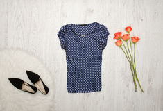Blue blouse with polka dots, shoes and orange roses on a wooden background. Fashionable concept Royalty Free Stock Photo