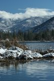 Blue on Blue. Winter scene reflected in mountain lake Royalty Free Stock Photos