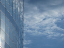 Blue in blue. Blue cloudy sky reflections on modern glass fascia Royalty Free Stock Photo