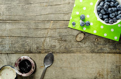 Blue. Berries on a bowl with green polka dot napkin placed on a rough textured table. And berry jam on the other side stock photography