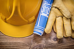 Blue blueprint hard hat protective gloves on wooden board constr Stock Images