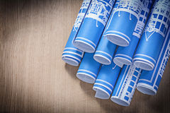 Blue blueprint rolls on wooden board top view construction conce Royalty Free Stock Photos