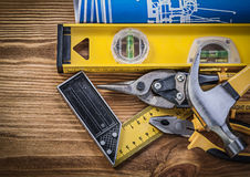 Blue blueprints construction level try square claw hammer pliers Stock Photos