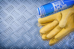 Blue blueprints safety gloves on channeled metal background cons. Truction concept royalty free stock photo