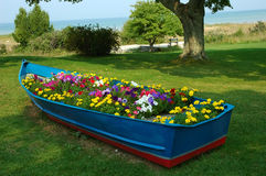 Blue Boat. An old row boat has been turned into a flower garden on the shore of Lake Michigan, USA stock images