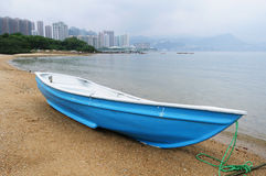 Blue boat on beach. A blue boat rests on a beach in suburb area Royalty Free Stock Photos