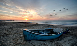 Blue Boat on Beach. Fishing boats at Durley Chine with Bournemouth Pier in background Stock Photography