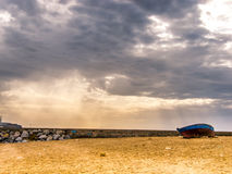 Blue boat on the beach. Dramatic weather Stock Photos