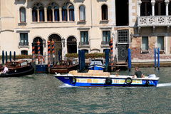 Blue boat with cardboard boxes in Venice, Italy Stock Photo