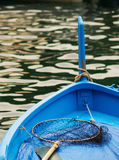 Blue boat detail. A blue boat with a net and water in the background royalty free stock photos
