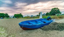 A blue boat and fishing net at sunset on a beach in Sunny Beach on the Black Sea coast of Bulgaria. Bulgarian clouds coastline day horizontal no people nobody royalty free stock images