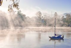 Blue boat on a foggy river. In a crisp morning Stock Photo