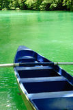 Blue boat on green tropical water.  Royalty Free Stock Photo