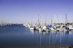 Blue boat harbour. Sailing boats mored in a harbour with reflections on the calm water Stock Photo