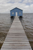 Blue boat house on river Stock Image