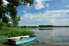 Blue boat on the lake shore. Blue wooden boat on the lake shore Stock Images