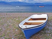 Blue boat on Nikolaiika Beach and the Corinthian Gulf, Greece. A blue boat sits on Nikolaika Beach near the waters of the Corinthian Gulf on the Peloponnesian Stock Images