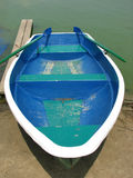 Blue boat with oars on the shore Stock Photo