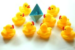 Cute yellow rubber ducks and one paper origami boat in blue color. stock photos