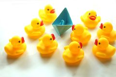 Cute yellow rubber ducks and blue paper ship. royalty free stock photo