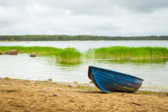 Blue boat on sandy shore. Hamina camping, Finland, Suomi. Blue rowing boat stands on a sandy shore in a quiet Bay of the Finnish Gulf. Area for summer camping in Royalty Free Stock Images