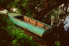 Blue boat in the shade of a tree by the river. A blue boat by the shore, a spring river, a photo postcard, a weeping willow, an old boat on the river, a green stock photography