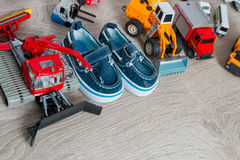 Blue boat shoes for boy near set of car toy on grey wooden background. Top view. Frame. Copy space. Stock Images