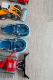 Blue boat shoes for boy near set of car toy on grey wooden background. Top view. Frame. Copy space. Stock Image