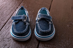 Blue boat shoes on brown wooden background. Boy footwear.  Stock Photography