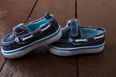Blue boat shoes on brown wooden background. Boy footwear.  Royalty Free Stock Photo