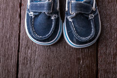 Blue boat shoes on brown wooden background. Boy footwear. Top view. Blue boat shoes on brown wooden background. Boy footwear. Top view Royalty Free Stock Image