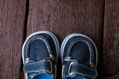 Blue boat shoes on brown wooden background. Boy footwear. Top view. Blue boat shoes on brown wooden background. Boy footwear. Top view Royalty Free Stock Photography