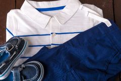 Blue boat shoes near shorts and white striped polo on brown wooden background. Boy outfit. Top view. Stock Image