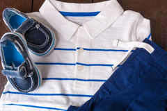 Blue boat shoes near shorts and white striped polo on brown wooden background. Boy outfit. Top view. Royalty Free Stock Image