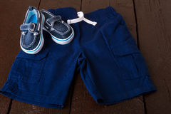 Blue boat shoes in shorts on brown wooden background. Boy outfit. Top view. Royalty Free Stock Photo