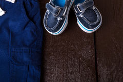 Blue boat shoes in shorts on brown wooden background. Boy outfit. Top view. Copy space. Royalty Free Stock Image