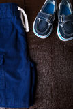 Blue boat shoes in shorts on brown wooden background. Boy outfit. Top view. Copy space. Stock Photography